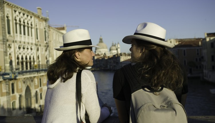 Two tourists conversing on a bridge in Venice, Italy.