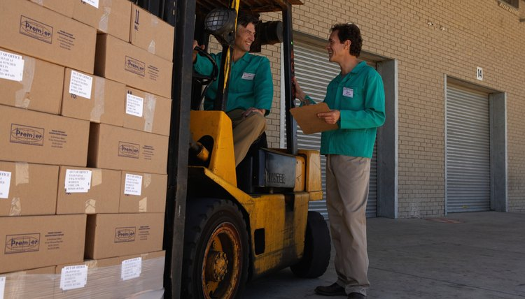 Two men working, one driving forklift, one holding clipboard