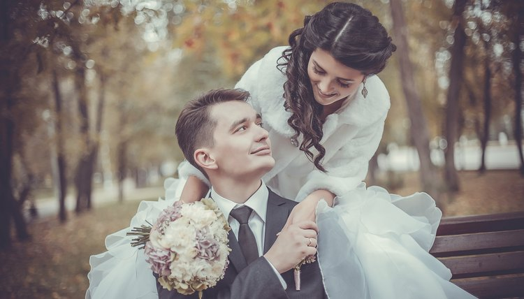 Bride and groom on a park bench in autumn.