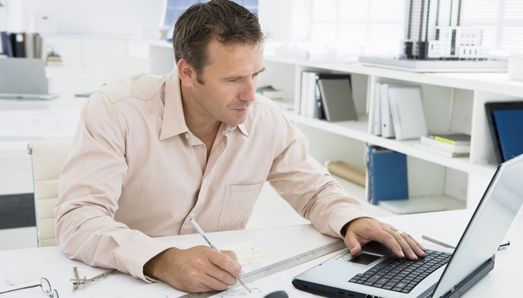 Man working on laptop in architectural office