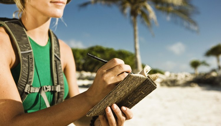 Woman sitting on beach writing in journal