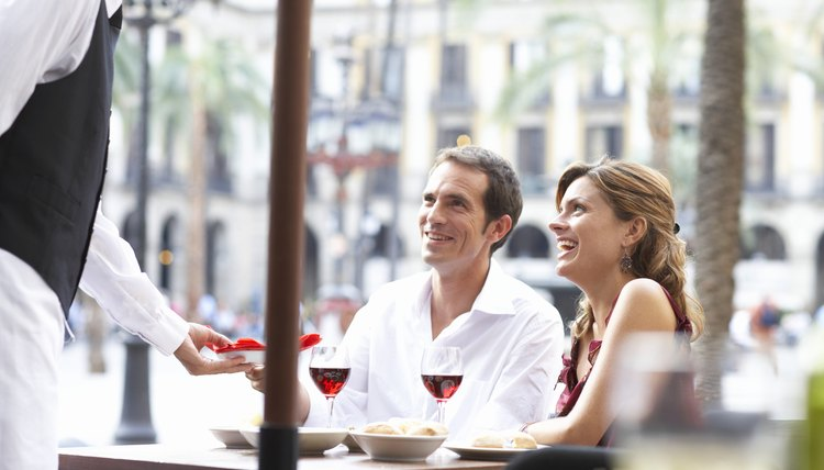 Waiter bringing food to couple at table in restaurant