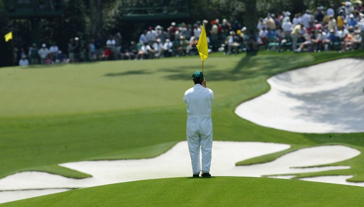 A forecaddie marks a ball's position during the 2004 Masters.
