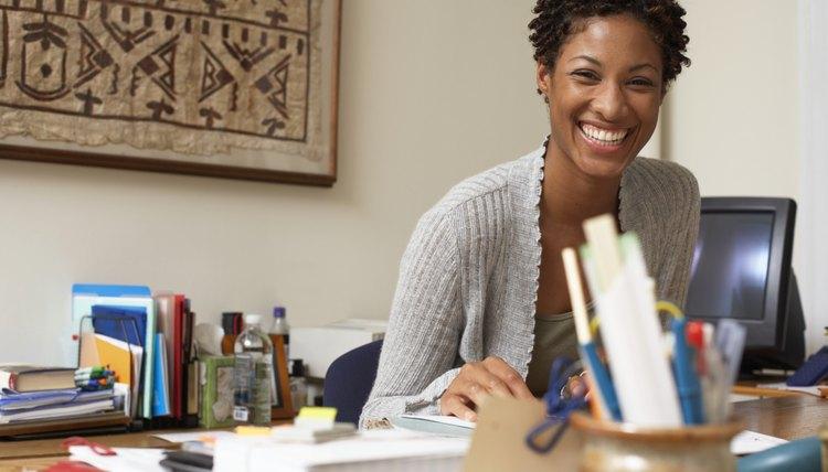 Female Office Worker Sitting At Desk Smiling Portrait