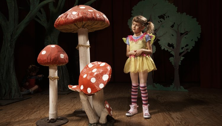 Girl (5-7) standing beside giant toadstools on stage