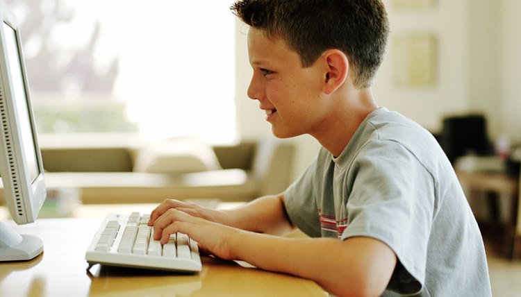Boy (9-11) at table using computer, profile