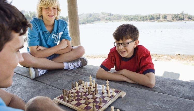 Campers and camp counselor playing chess