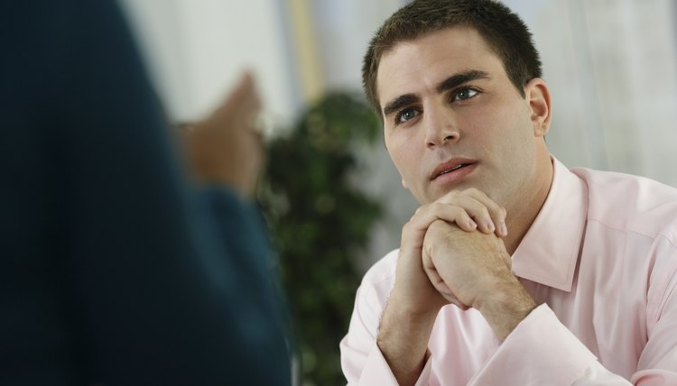 Middle Eastern businessman listening to coworker
