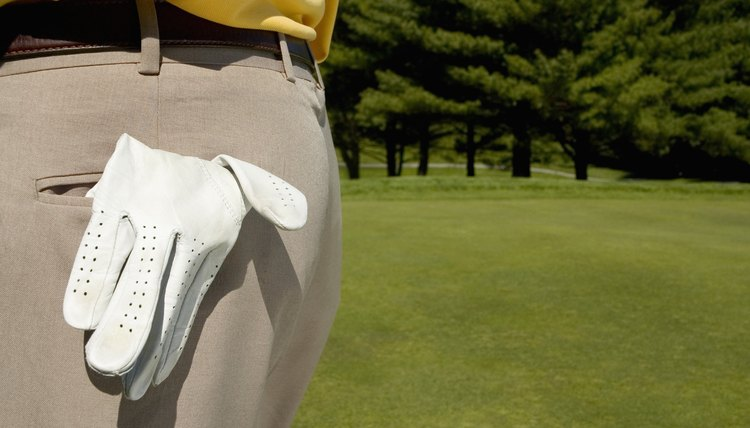 Some golfers store their golf glove in a back pocket while putting.