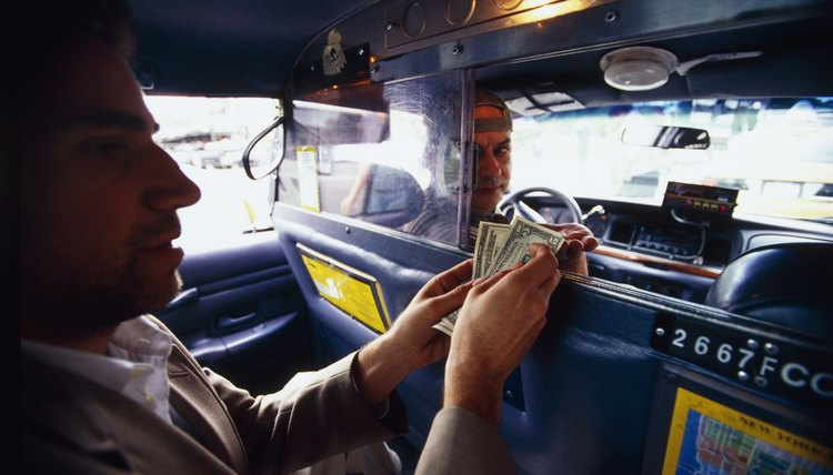 A passenger pays a taxi driver.