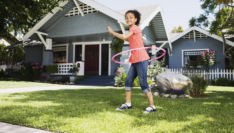 Young girl playing with a hula hoop.
