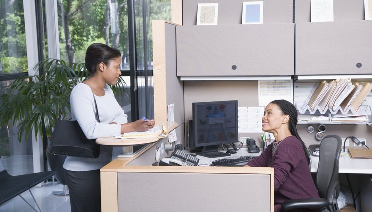 Woman talking with secretary in office, side view