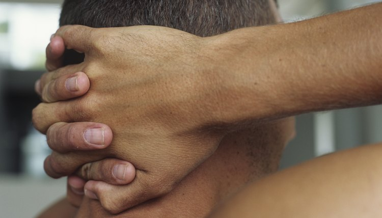 Man holding hands behind neck,close-up,rear view