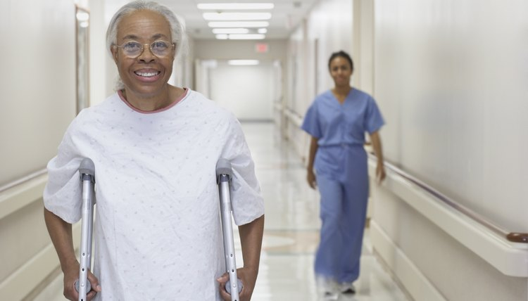 Senior African woman walking on crutches in hospital corridor
