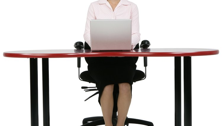 Professional Woman Sitting at Desk with Laptop Computer
