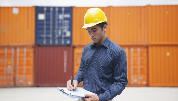 Smiling young engineer in protective work wear in a shipping yard examining cargo and writing on clipboard