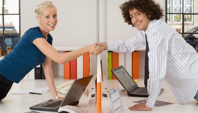Businesspeople shaking hands over cubicle divider
