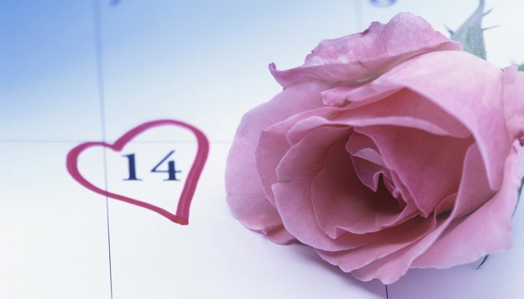 A rose on a calendar with a heart marking Valentine's Day.