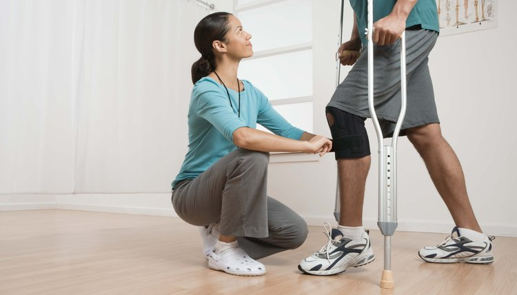 Physical therapist helping patient with crutches