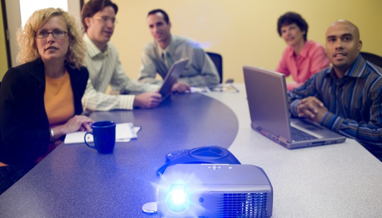 Employees wrapping up a PowerPoint presentation in a conference room.