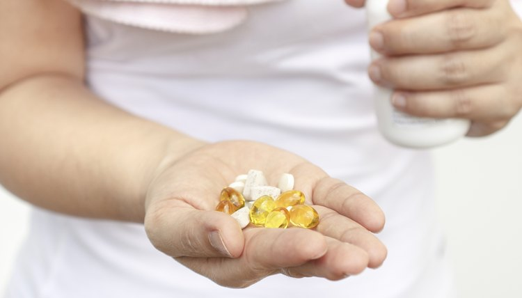 Woman hand with Cod liver oil and supplements