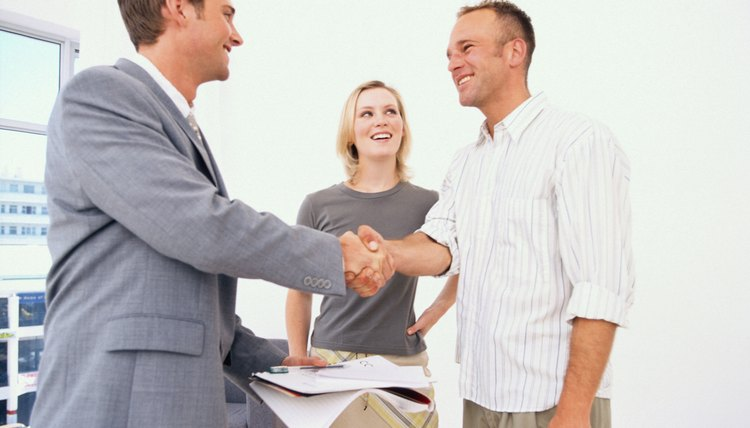 Sales consultant shaking hands with business owners