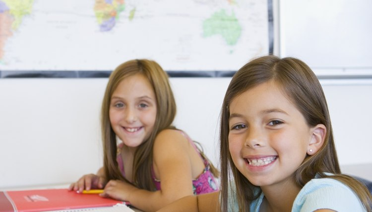 Young girls sitting at table in classroom.