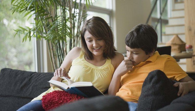 Woman reading book with boy