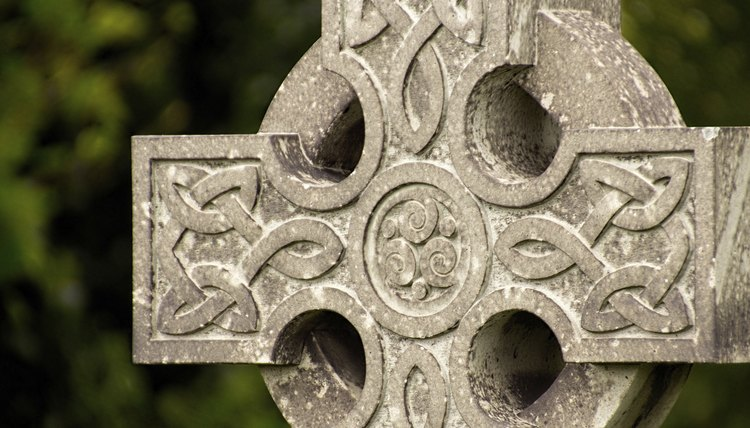A close-up of an aged stone Celtic cross outdoors.