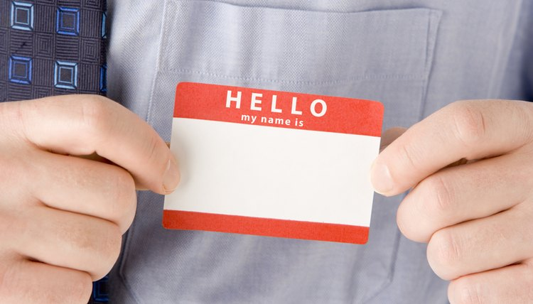 A man holds a blank name tag.