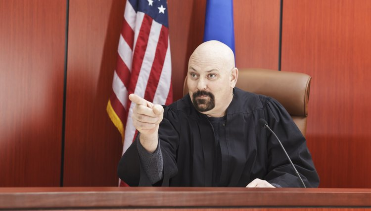 Male Judge Pointing While Seated in Courtroom