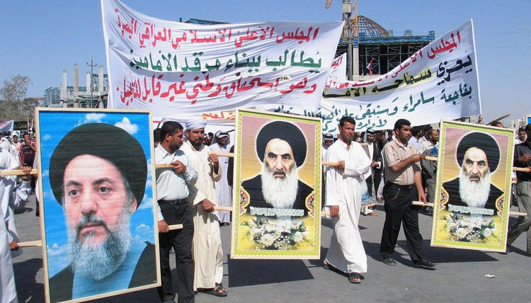 Shiite Muslims carry pictures of one of their major religious leaders, Grand Ayatollah Ali al-Sistani, during a protest.