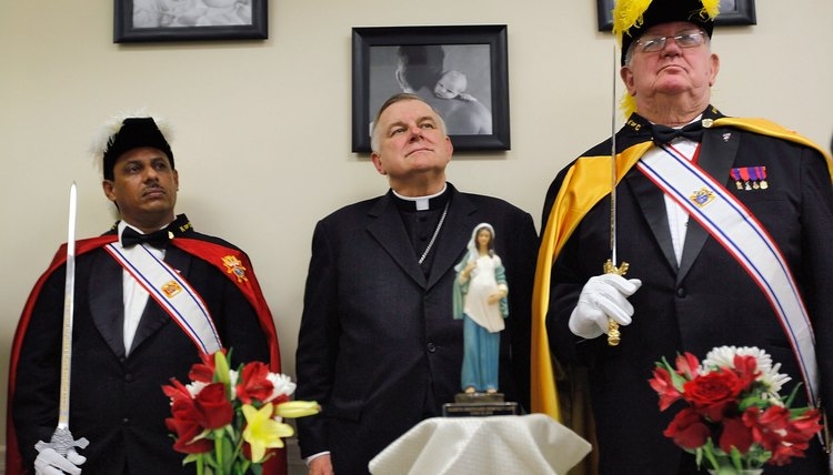 The Miami archbishop is flanked by two members of the Knights of Columbus, a Catholic fraternal order.