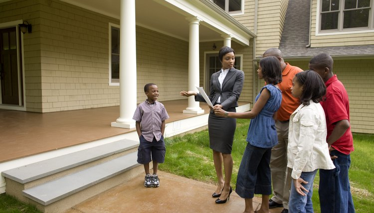 Realtor showing family around house for sale