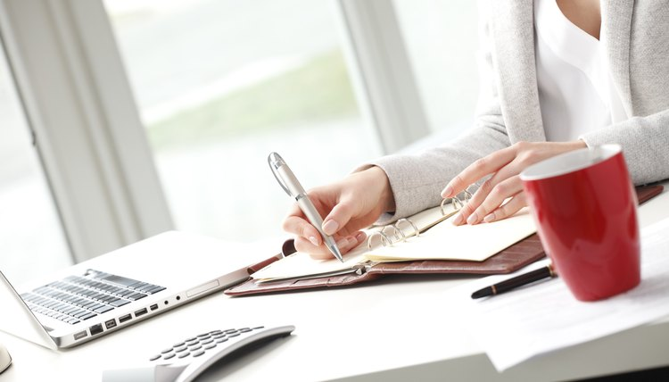 Businesswoman sitting at desk and makes a note in office.