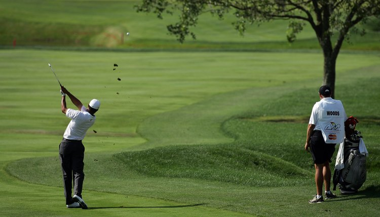 Tiger Woods fades the ball, shaping it around a tree.
