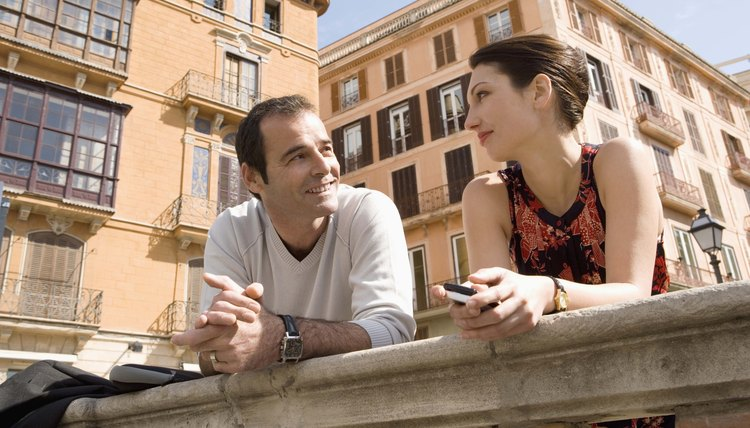Two people conversing outdoors on a bridge.