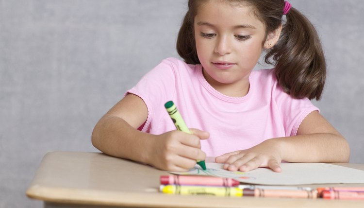 Young girl coloring at table.