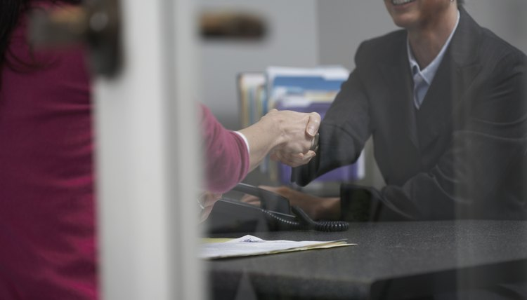 Two women shaking hands over desk in office