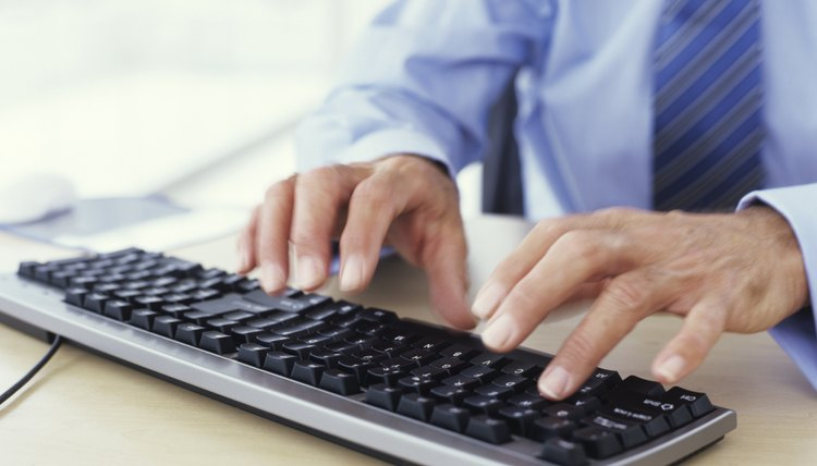Man using keyboard, close up, mid section