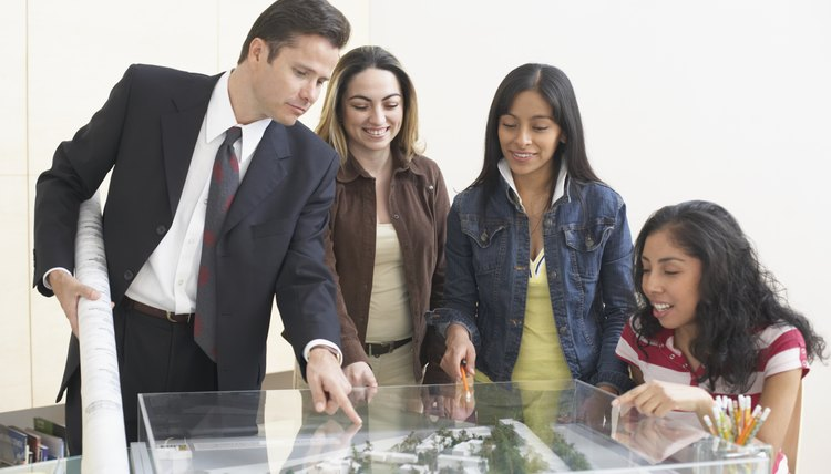 Four architects looking at the model of a building complex