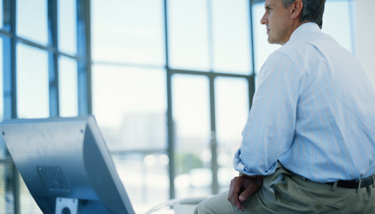 Businessman sitting on desk with computer, looking away, side view