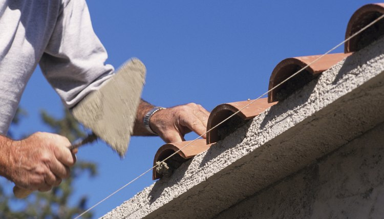 Builder laying roof tiles