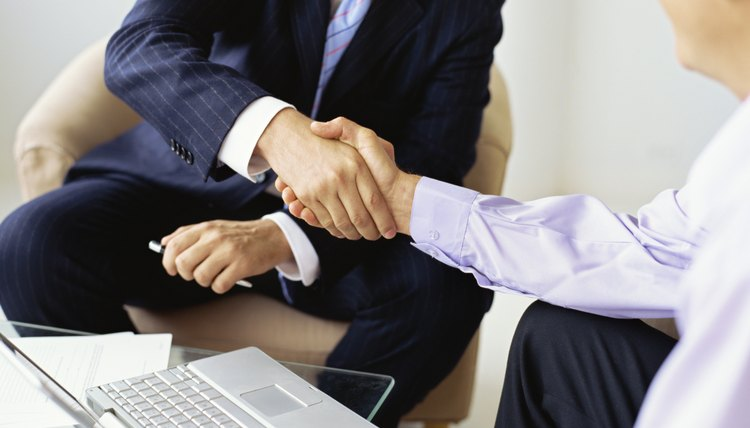 male real estate agent shaking hands with a mid adult man