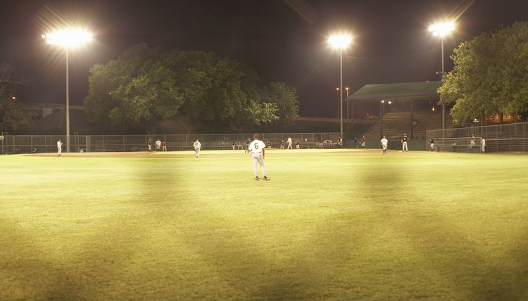 Baseball game under artificial lightning through chainlink fence
