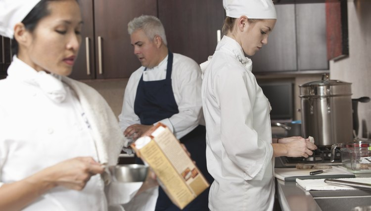 Three chefs work together in busy kitchen