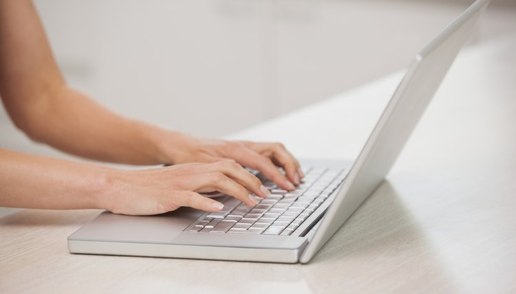 Side view of hands using laptop