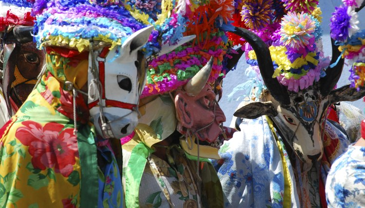 People in a parade wear Mexican masks and costumes.