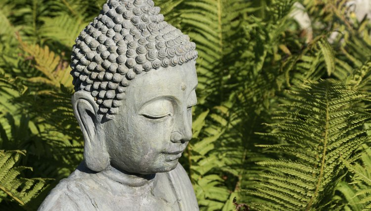 A Buddha statue in the garden with elongated ear lobes.