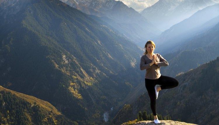Woman doing yoga on a mountain summit